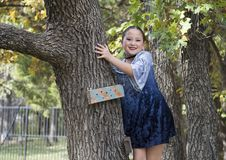 Amerasian girl posing in the trees in Oklahoma City, Oklahoma. Pictured is a 9 year-old Amerasian girl posing in a tree in Oklahoma City, Oklahoma.  She will Royalty Free Stock Photo
