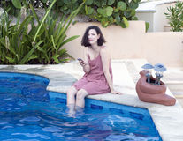 Amerasian beauty relaxing on the edge of a swimming pool Stock Photo