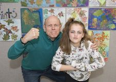 Grandfather in tough guys pose with granddaughter. Pictured is a 70 year old grandfather with his eleven year old granddaughter.  They are both scowling Royalty Free Stock Images