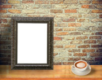 Pictureframe. Blank picture frame put on wooden tabletop with coffee cup on vintage brick background Stock Photos