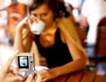 Pictures at the coffee table. Camera in hands taking pictures of a woman drinking coffee at the table royalty free stock photography