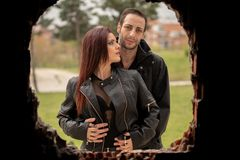 Photo shoot for a couple of redheaded women and brown men. Pictures of a couple in black and hard looking clothes in different settings stock image