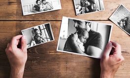Pictures of father and daughter, wooden background. Fathers day. Hands of unrecognizable men holding pictures of young father and his little baby daughter royalty free stock images