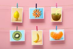 Pictures with fruits hanging on a linen thread on stationery on clothespin on a colored background, concept of cheerful mood, royalty free stock photos