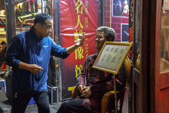 Pictures of the man and the wax. Pingyao, shanxi, china - the blue dress man and focus on taking pictures in front of the wax museum Royalty Free Stock Images
