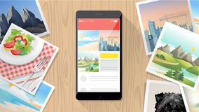 Pictures and mobile on table. Pictures camera app on smartphone with instant pictures all around Royalty Free Stock Image