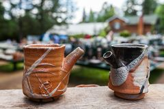 Two pottery teapots that look like clay cups stock images