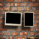 Pictures on a rope with clothespins, with clipping path for images, in front of a brick wall Stock Image