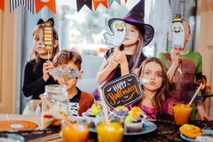 Boys and girls wearing costumes holding pictures and signs devoted to Halloween royalty free stock photography
