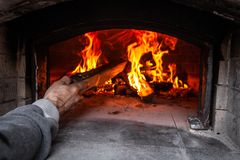 Bread oven with a fire inside, while man is adding some wood to the fire royalty free stock photos