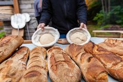Man is showing 2 ready to cook bread doughs stock images