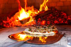 Man is placing a freshly prepared pizza into an outdoor bread oven - stock image