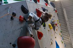 Young man climbing on an advanced climbing wall indoors royalty free stock photography