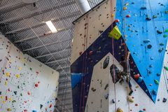 Young man wearing colorful clothing climbing on an climbing wall indoors stock images
