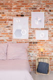 Pictures on the wall. Pictures on the red brick wall in cozy bedroom Stock Photography
