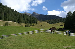 Picturesque Alpine landscape. Scenic view of picturesque Alpine landscape with people walking over field in foreground royalty free stock images