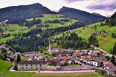Picturesque alpine village in Italy. Picturesque alpine village with a church tower. A few building is surrounded by green meadows and forests at slopes. Italy royalty free stock photo