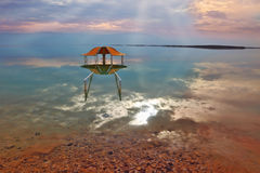 The picturesque arbor for bathers. Is reflected in a smooth sea surface. Fantastically beautiful optical effects at the Dead Sea Stock Photo