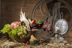 Picturesque autumn composition with basket, fruits, pumpkin, win. E, and wine glass, with hay on old wooden background Royalty Free Stock Images