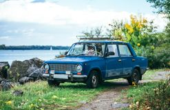 Autumn in UK. Old car on the lake shore royalty free stock image