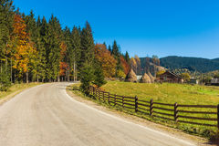 Picturesque autumn road in mountain village. In Ukrane Carpathians. Clear blue sky Royalty Free Stock Images