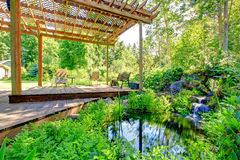 Picturesque backyard farm garden with small pond and patio area Royalty Free Stock Images