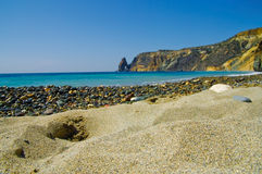 Picturesque beach. Low angle view of picturesque stony beach with grainy sand in foreground Royalty Free Stock Photography