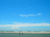 Picturesque beach and blue sky. Scenic view of two people in sea with picturesque beach and blue sky background Royalty Free Stock Photos