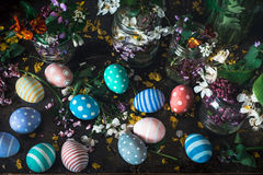 Picturesque bouquets of colorful spring  flowers in glass vases bottles and colorful handmade paint easter eggs on a dark wooden Royalty Free Stock Photography