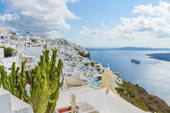 Picturesque cactuses and romantic greek houses above the bay, with panoramic view on caldera. Santorini island. Stock Photos