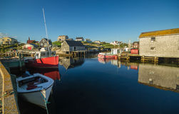 Picturesque Canadian fishing village. Wide angel view of colorful boats and fishing shacks and reflections in the water at the tranquil,quaint,fishing village of Royalty Free Stock Images