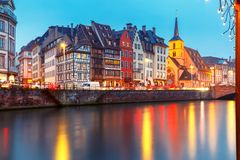 Christmas embankment in Strasbourg, Alsace. Picturesque Christmas quay and church of Saint Nicolas with mirror reflections in the river Ile during evening blue Stock Photos
