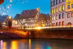 Christmas embankment in Strasbourg, Alsace. Picturesque Christmas quay with mirror reflections in the river Ile during evening blue hour, Strasbourg, Alsace Stock Image