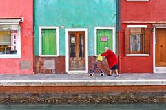 Picturesque cityscape with elderly woman walks with a cart tutor along the water canal in Burano island with the backg royalty free stock photos