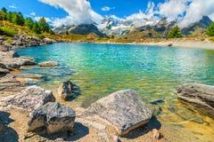 Stunning alpine lake and snowy mountains with glaciers, Zermatt, Switzerland. Picturesque clean alpine pond with high snowy mountains in background, Zermatt royalty free stock photos