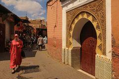 Picturesque corner. Street scene. Marrakesh. Morocco. A woman walking by a colorful  doorway in the souk.  Marrakesh. Morocco Stock Image