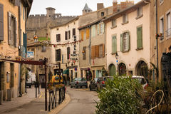 Picturesque corner in village. Carcassonne. France. Picturesque corner in the modern village. Rue Trivalle. Medieval walled citadel in the background Royalty Free Stock Image