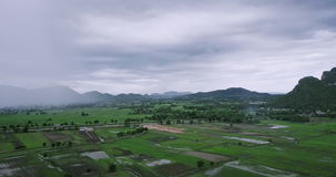Picturesque countryside landscape panorama with view of green field and mountains on rainy day in Thailand stock video