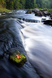 Picturesque countryside river. Picturesque river in countryside with slow motion blur effect, single Autumnal leaf on rock in foreground Stock Photography