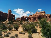 Double Arch and rock formations at Arches National Park. Picturesque desert scene with Double Arch, rock formations, bushes, and clouds in Arches National Park royalty free stock image