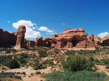 Rock formations at Arches National Park. Picturesque desert scene with rock formations, bushes, and clouds in Arches National Park Stock Images