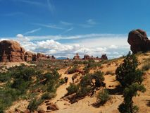 Picturesque desert scene with rock formations, bushes, and clouds. In Arches National Park stock images