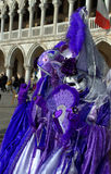 Picturesque disguised people Venice. Street performers in splendid purple costumes during the Venice Carnival days and tourists.Venice Italy,Photo taken on Stock Photography