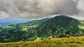Picturesque and dramatic Carpathian mountains under huge rain clouds, nature landscape in summer, Ukraine. Royalty Free Stock Images