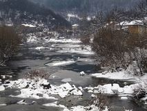 Snowy winter village elevated view from a bridge to a river and old riverbank houses royalty free stock images
