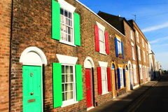 Colorful shutters English town houses. Brown brick houses with bright colourful painted window shutters,Deal town England Stock Photo