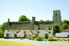 Picturesque english village scene. Idyllic village scene of an historic thatched public house with St Mary Magdalene village church in the background on the stock photography