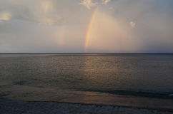 Picturesque evening sky with a rainbow over the dark Baikal water Royalty Free Stock Photo