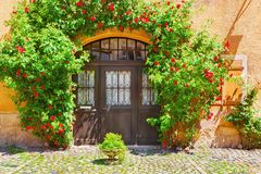 Picturesque facade of old building in Kaysersberg, Alsace, France. Picturesque facade of old building with arched door, window and decorated with flowers and Royalty Free Stock Image