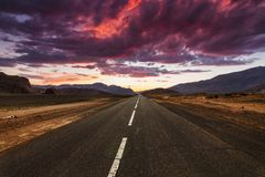 Picturesque fiery sunset over the cracked desert road Royalty Free Stock Images